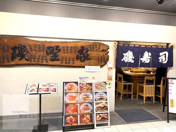 寿司の写真と看板がある、豊洲市場「磯寿司」の入り口